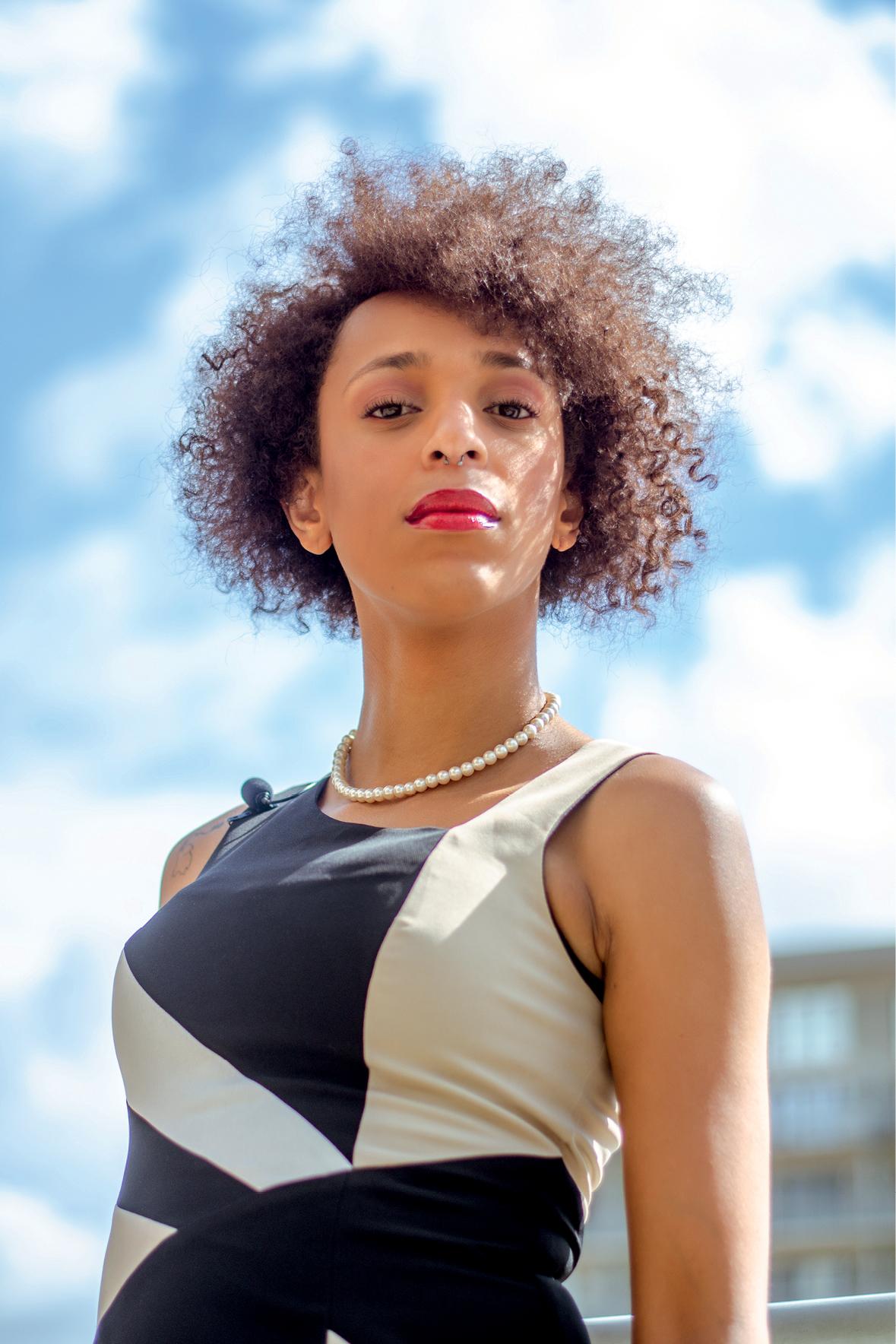 Érika é uma mulher negra de cabelos cacheados curtos. Ela usa uma blusa preta e branca e um colar. Usando batom vermelho, olha para a câmera sem sorrir.