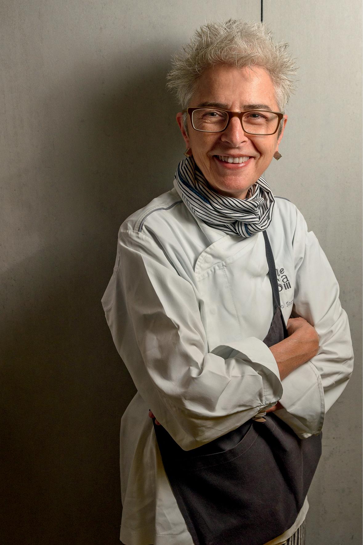 Ana é uma mulher branca com cabelos grisalhos bem curtinhos. Ela usa óculos e seu uniforme de chef de cozinha. Está com os braços cruzados e olha sorrindo para a foto