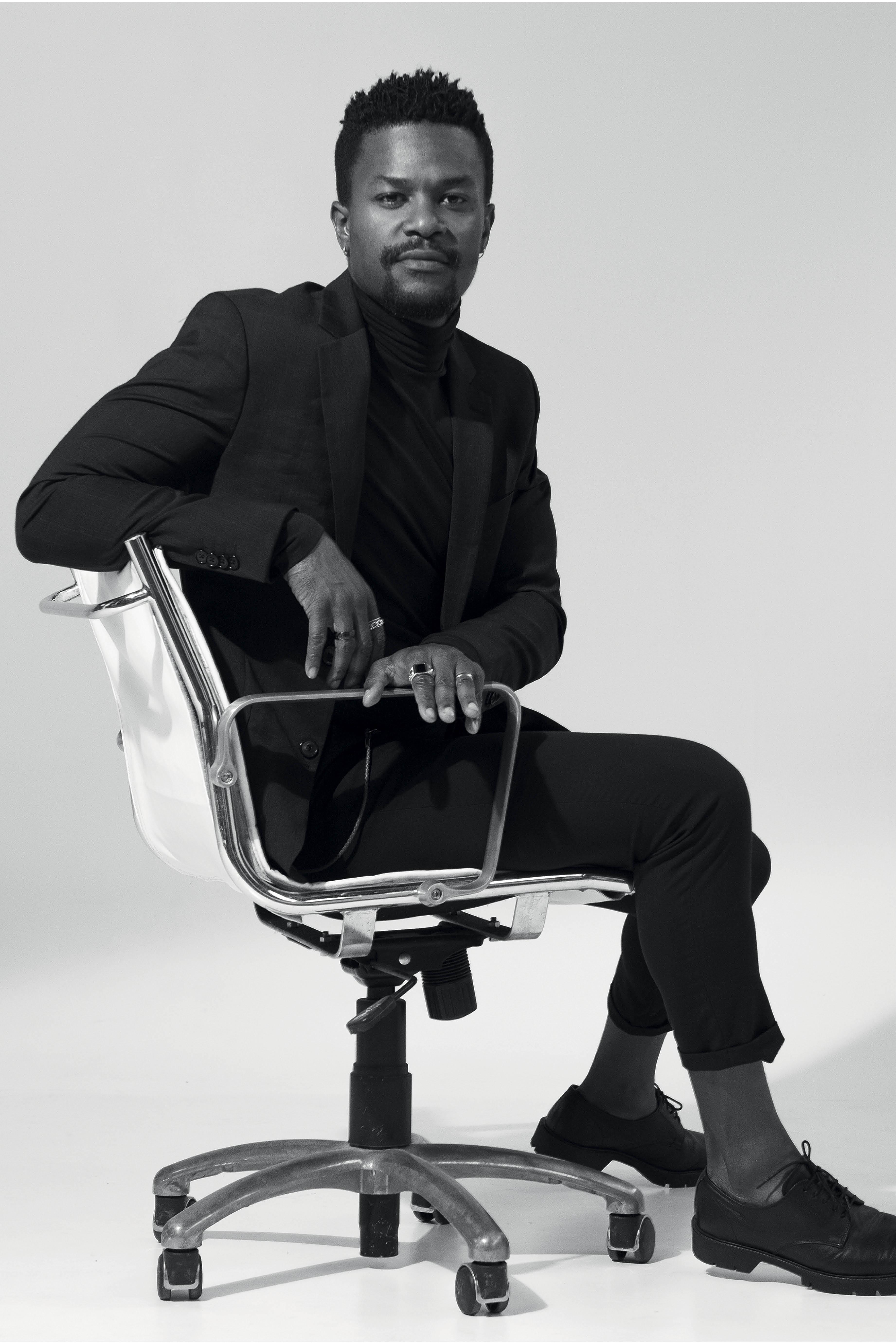 David é um homem negro de cabelo raspado. Ele está vestindo um terno e sentado numa cadeira