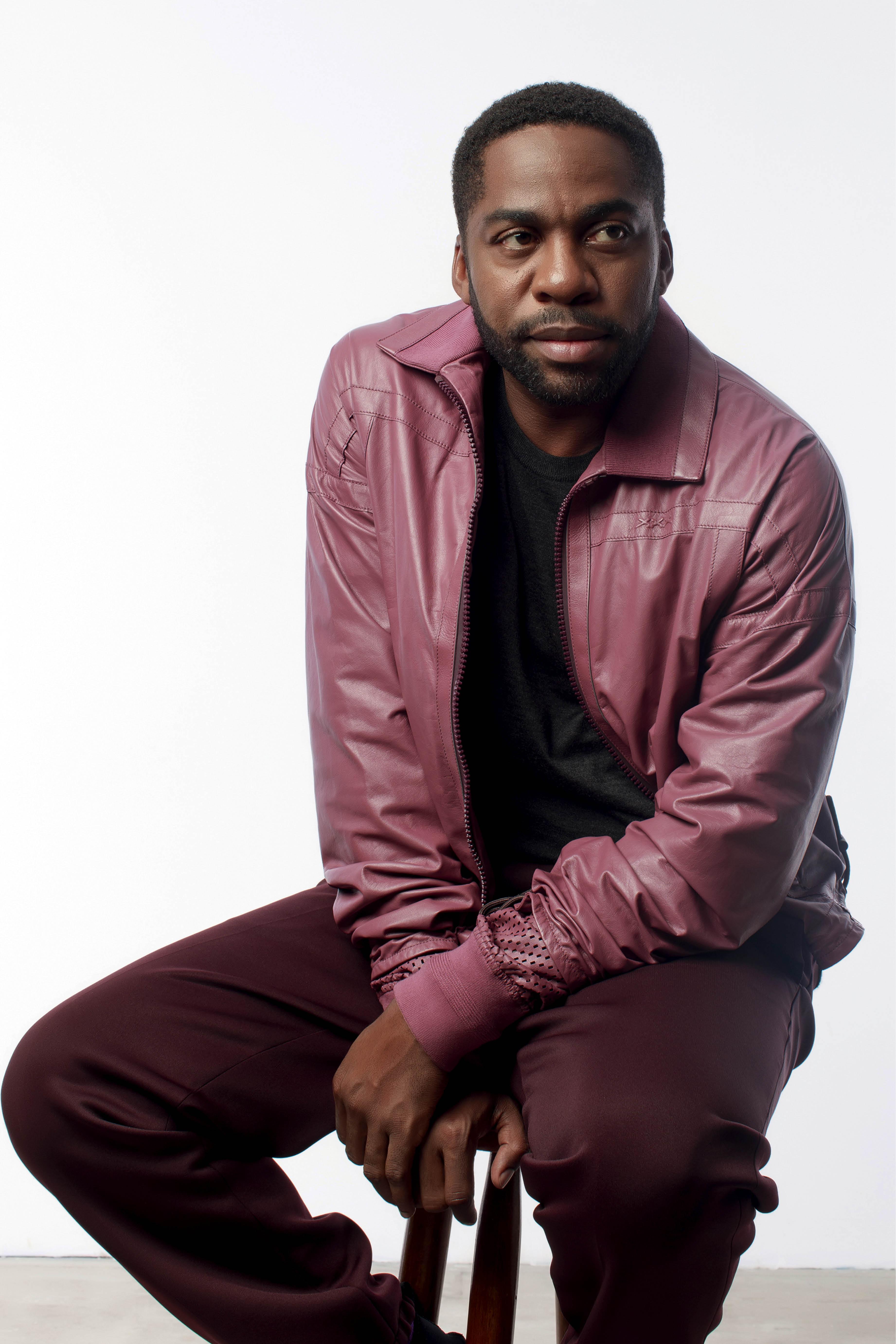 Lázaro é um homem negro, com cabelos curtos, barba e cavanhaque. Ele usa uma calça vinho e uma jaqueta rosa
