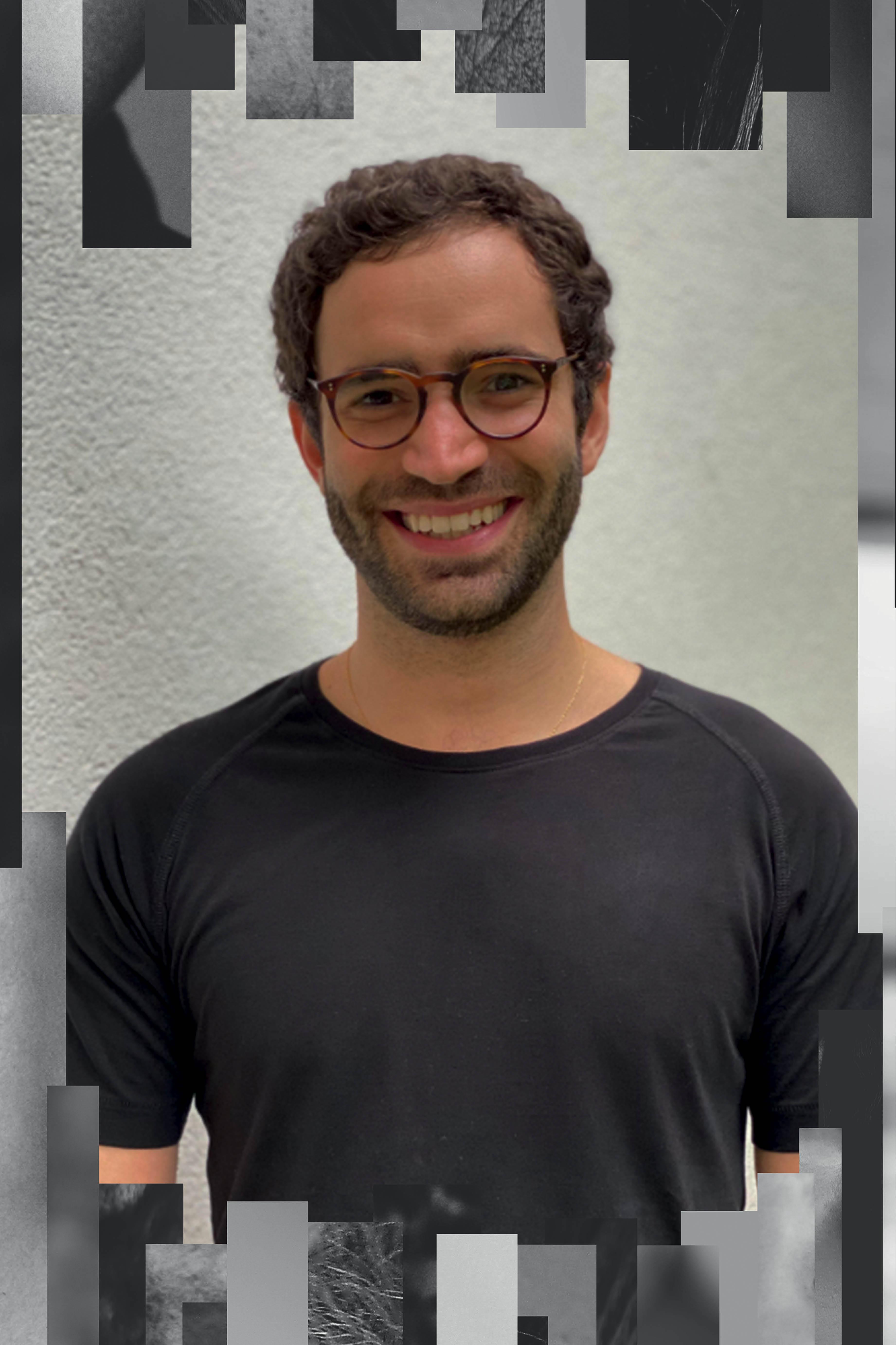 Pedro é um homem branco, de cabelos claros, barba e cavanhaque. Ele usa óculos e sorri para a câmera