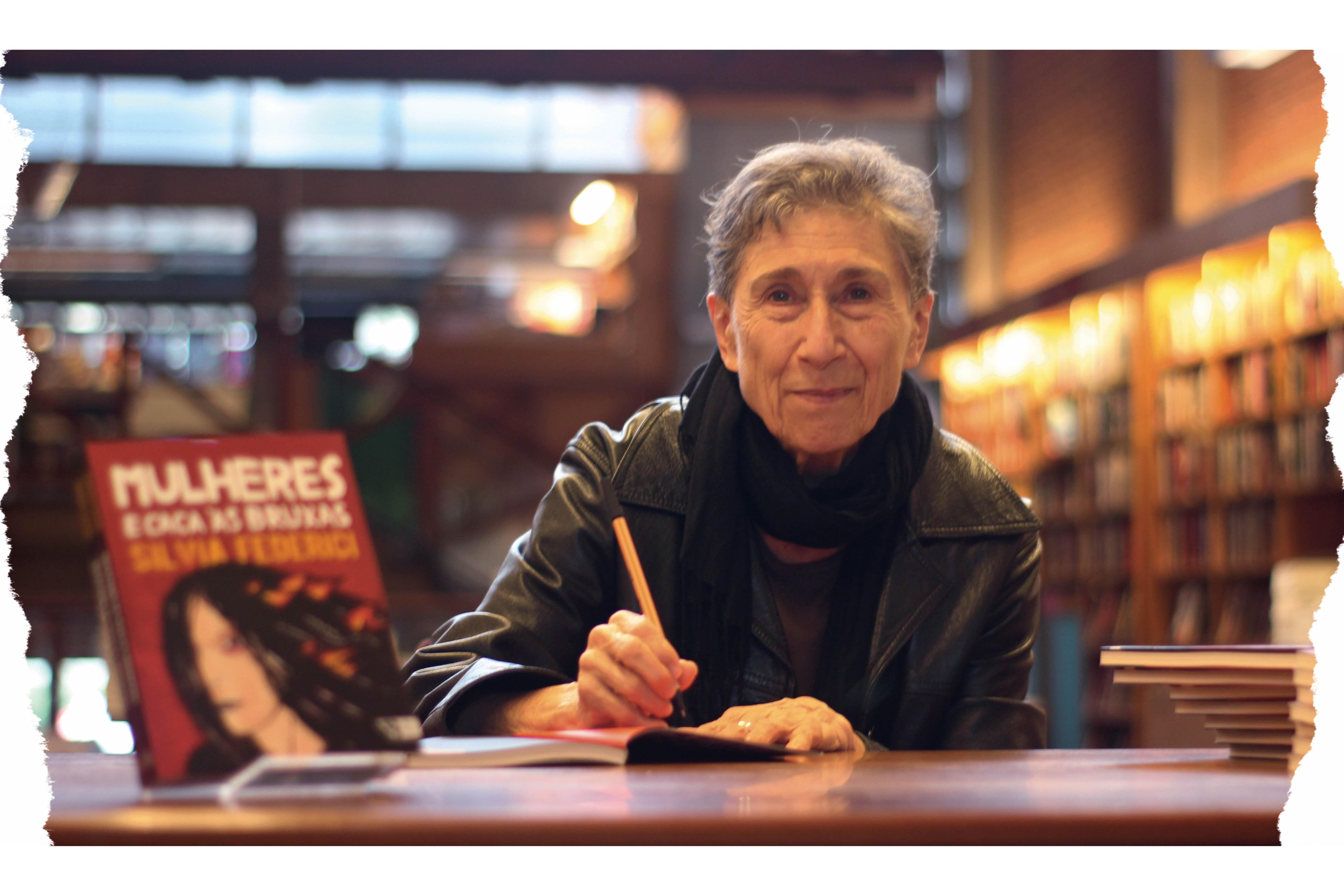 Silvia é uma mulher de cabelos curtos e grisalhos. Ela está sorrindo para a foto num cenário de livraria, enquanto autografa livros