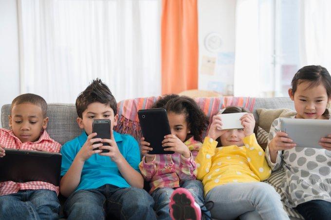 crianças usando celular tablet