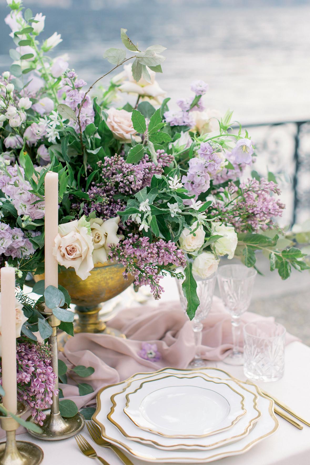 Detalhe da mesa de festa com panos lilás, velas e flores brancas e lilás
