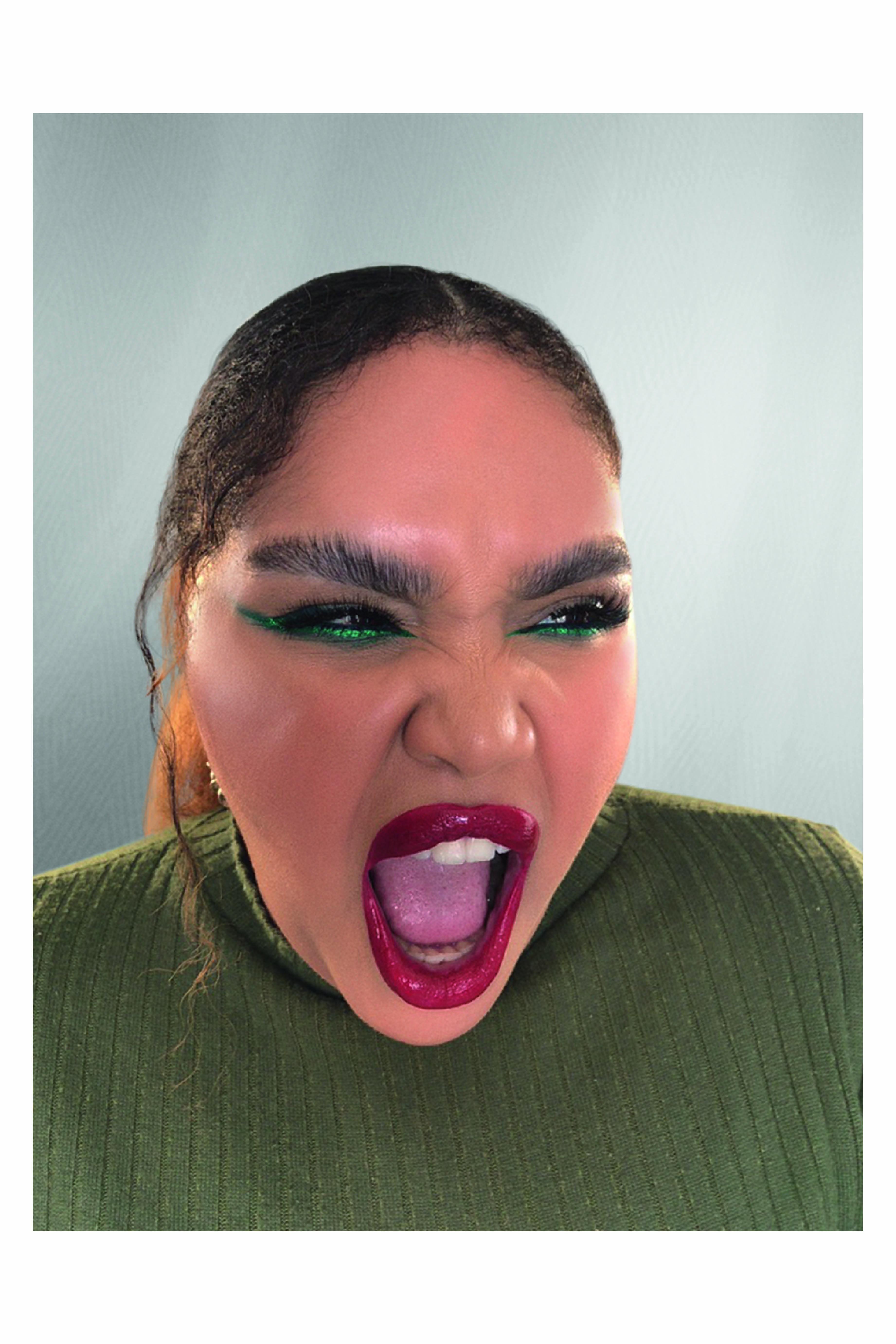 Mulher com olho delineado verde e batom vermelho olha para a câmera