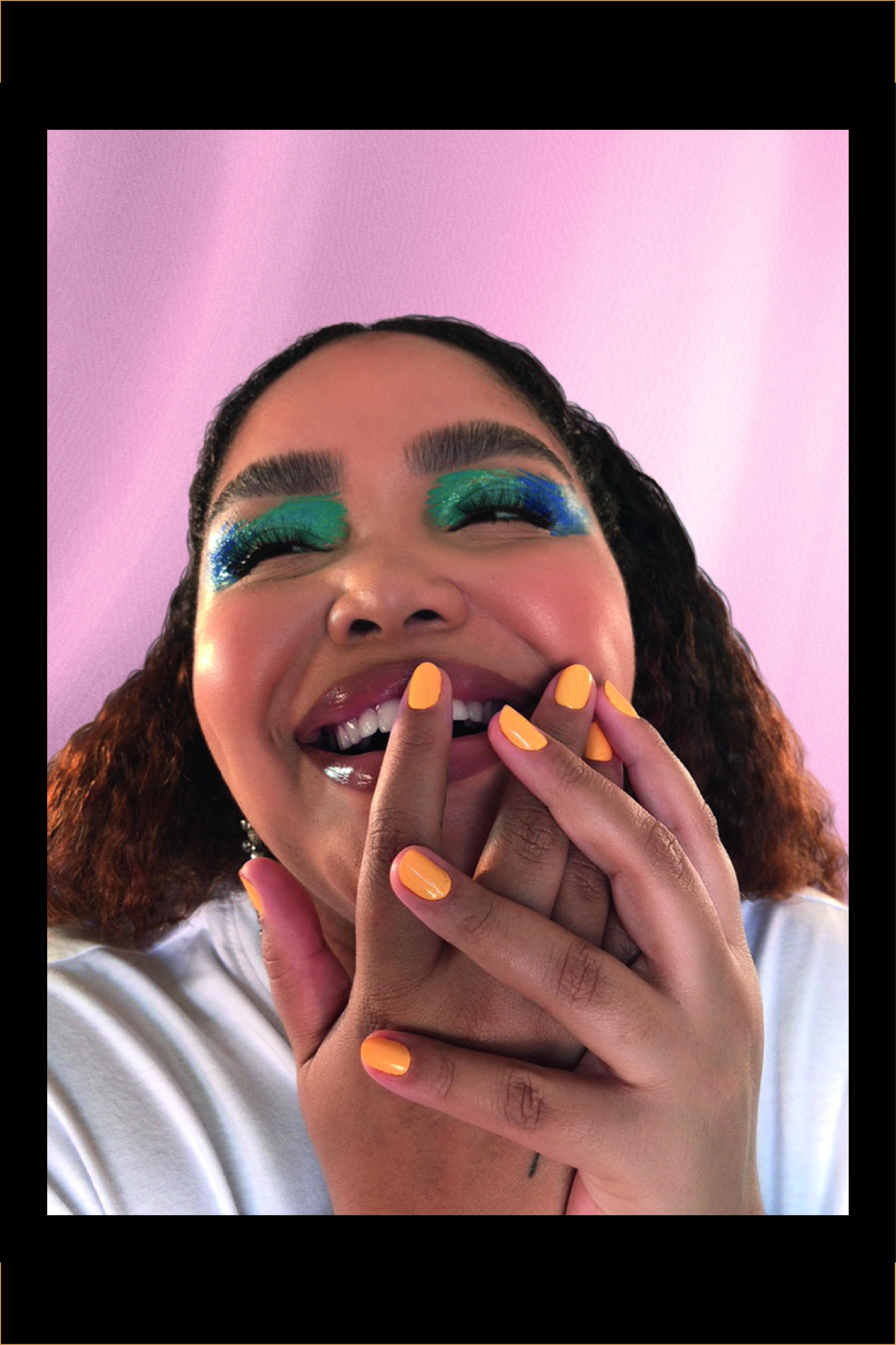 Mulher com os olhos maquiados com sombra azul e unhas pintadas de amarelo dá risada