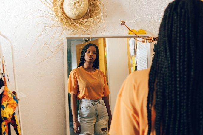 mulher negra de frente para espelho