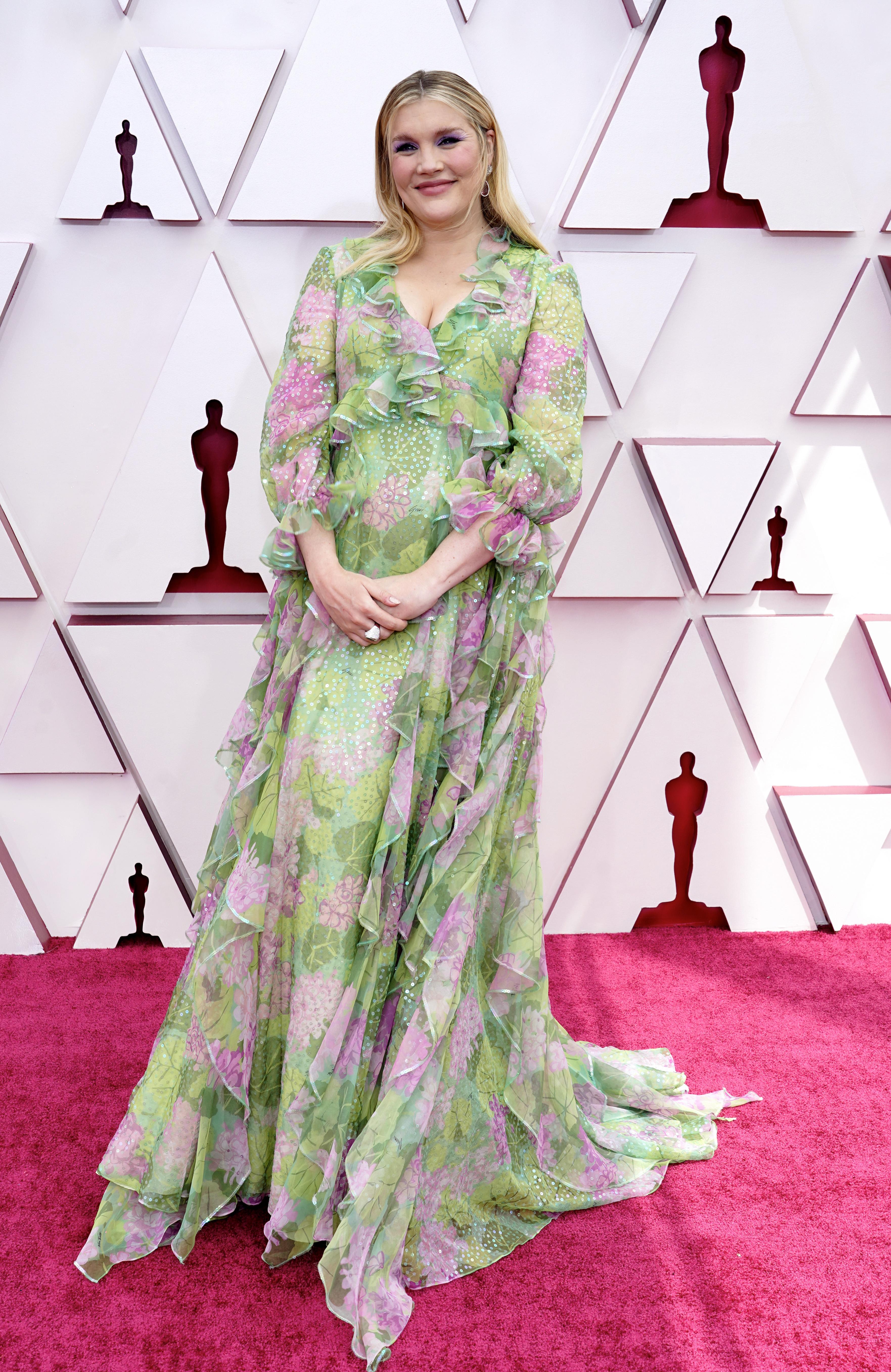 Emerald é uma mulher branca com cabelos loiros. Ela está grávida. Usa um vestido verde com flores cor-de-rosa, mangas longas e fluido, bem romântico
