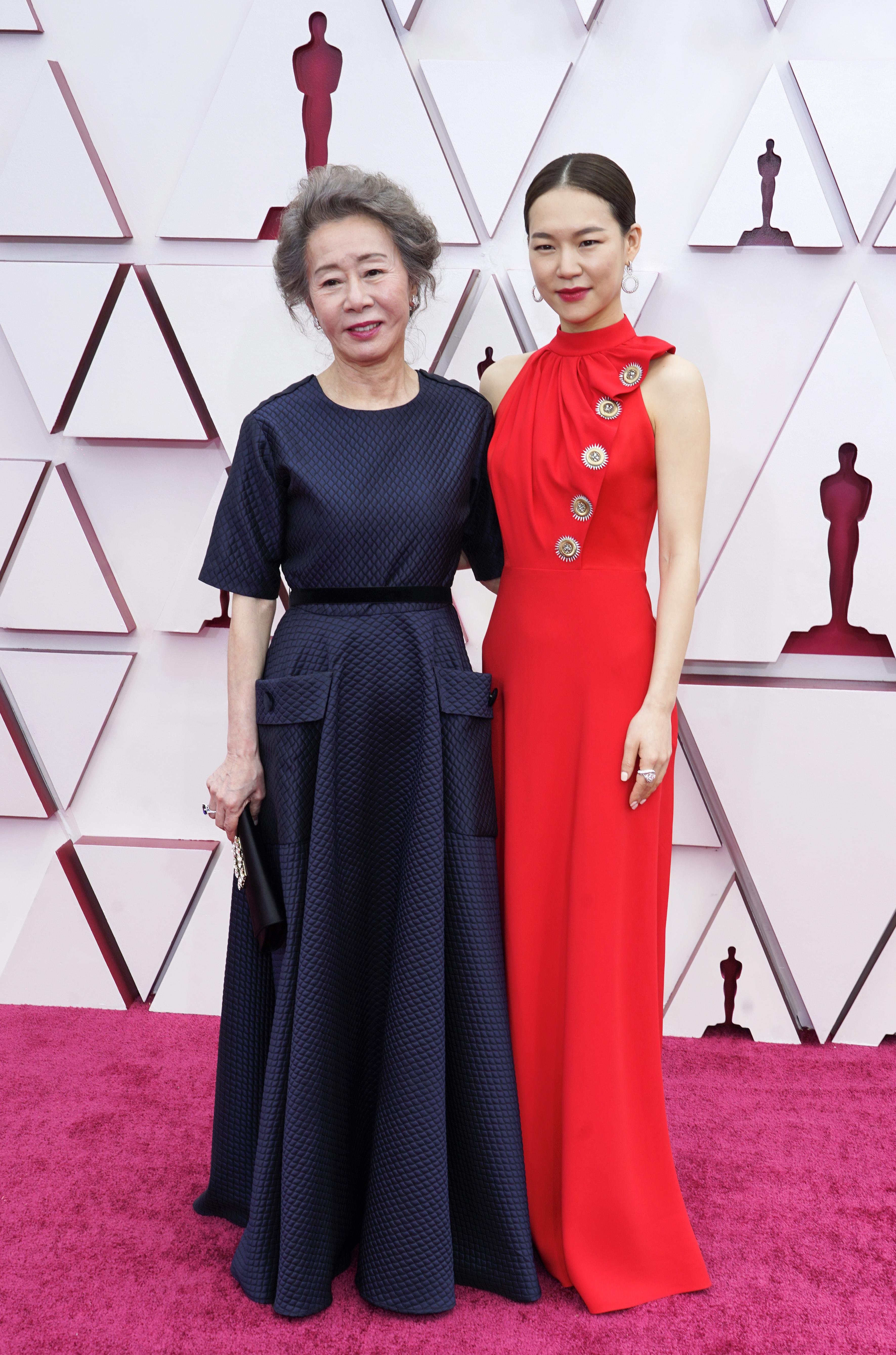 As atrizes são orientais. Do lado esquerdo, Youn tem cabelos grisalhos presos. Ela usa um vestido com mangas curtas tipo camiseta, azul marinho. Já Han usa um vestido vermelho com gola alta, sem mangas e detalhes dourados