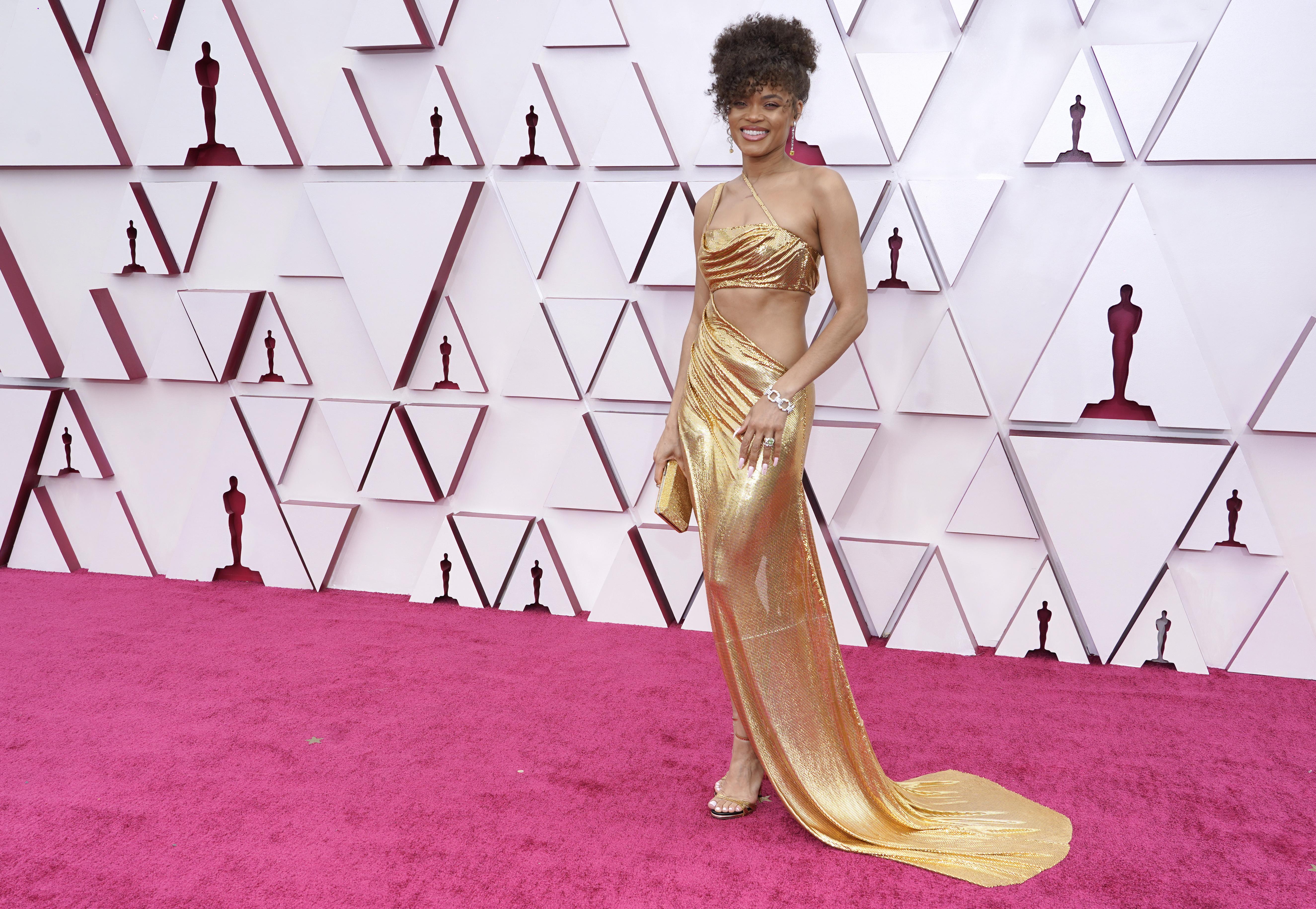 Andra é uma mulher negra, com cabelos castanhos cacheados presos. Ela usa um vestido dourado com recorte abaixo do seio e por toda a lateral do torso.
