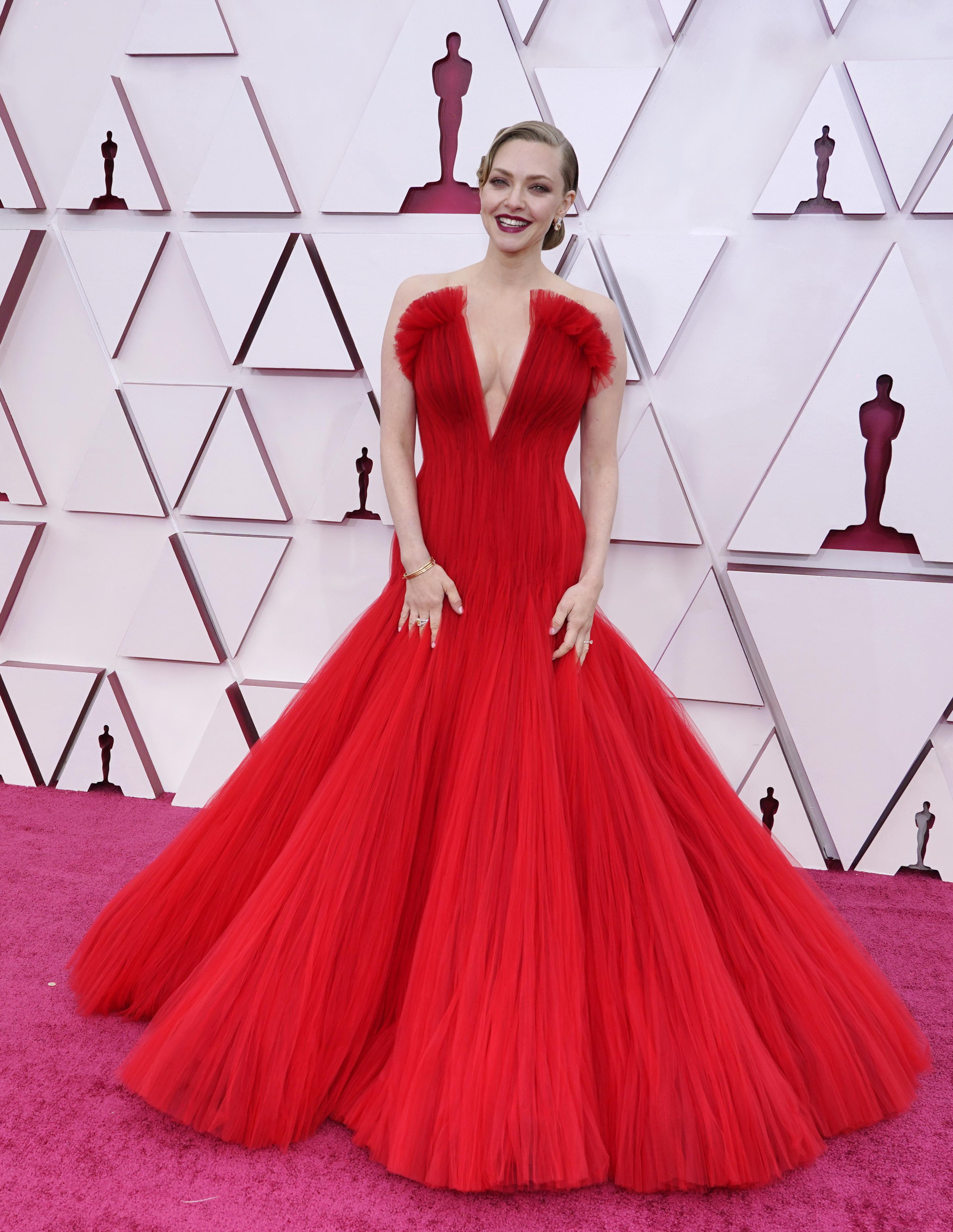 Amanda é uma mulher branca, loira. Ela usa um vestido vermelho com volume no decote, que desce em V até a barriga e saia volumosa