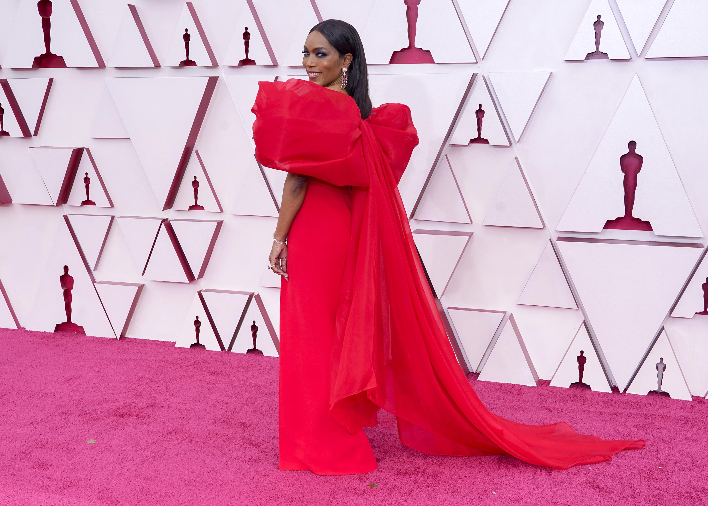 Angela é uma mulher negra com cabelos castanhos lisos e longos. Ela usa um vestido vermelho com laço enorme nas costas