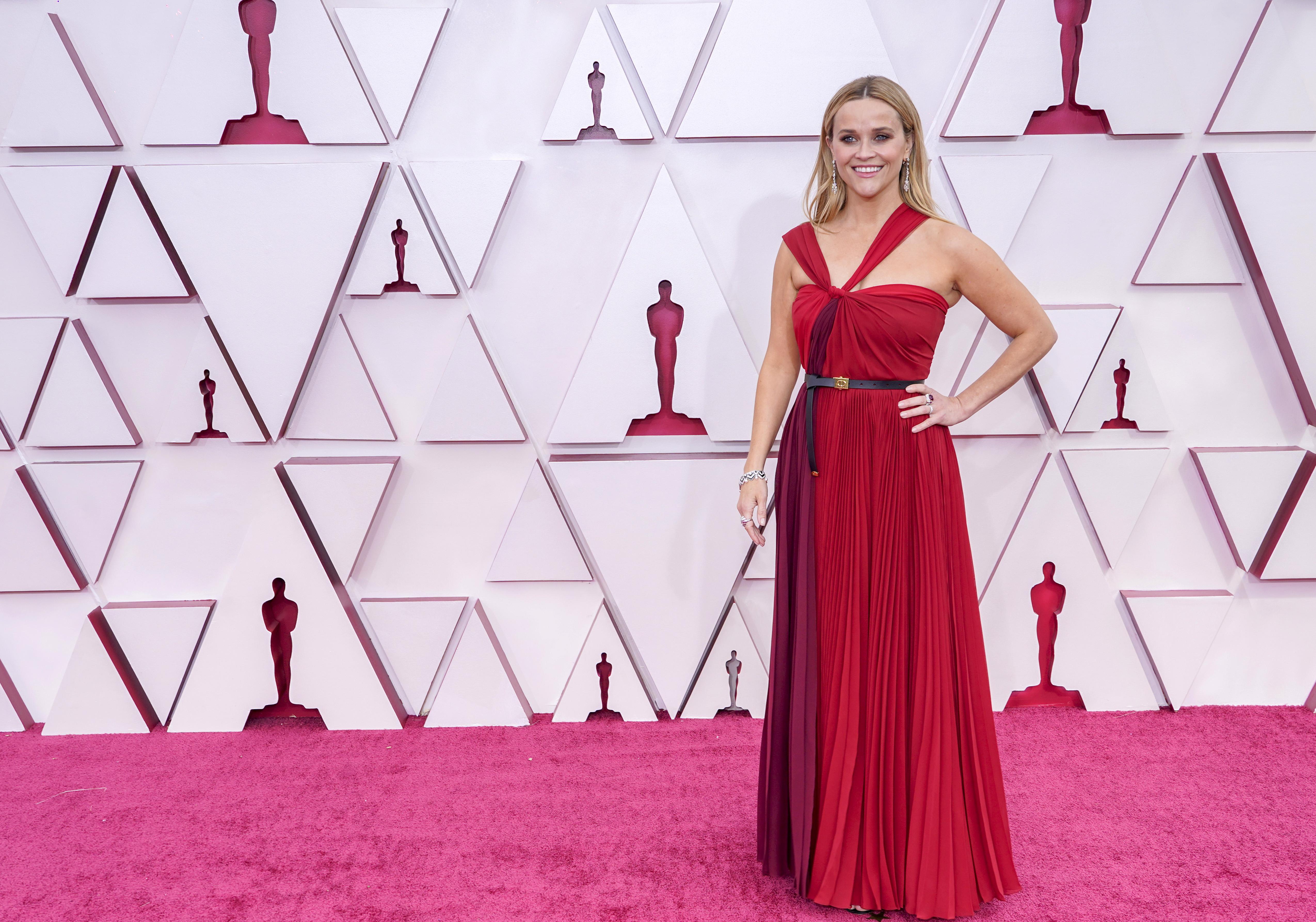 Reese é uma mulher branca, loira, com um vestido em vários tons de vermelho com a cintura marcada por um cinto preto