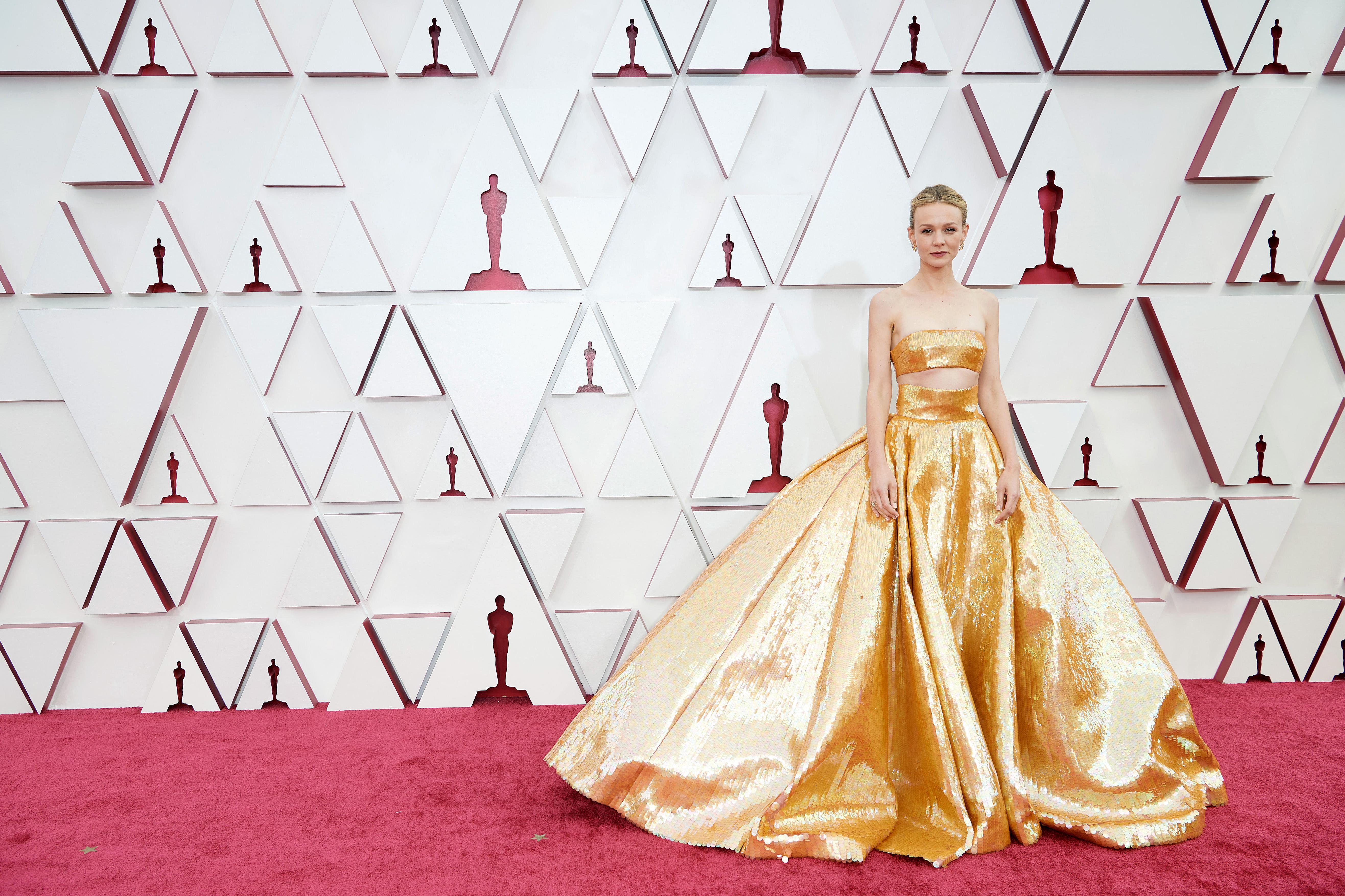 Carey é uma mulher branca, loira, com um vestido de saia volumosa dourado e recorte logo abaixo dos seios
