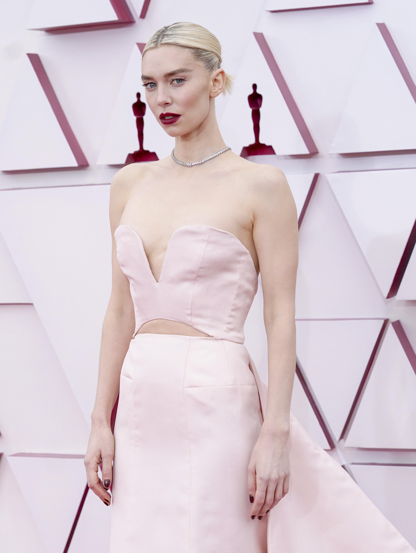 Vanessa é uma mulher branca e com cabelo loiro platinado. Ela usa um vestido rosa bem claro sem mangas, com decote coração e um recorte na área da barriga