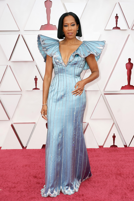 Regina é uma mulher negra, de cabelos castanhos na altura do ombro. O vestido dela é azul claro, justo com mangas bufantes
