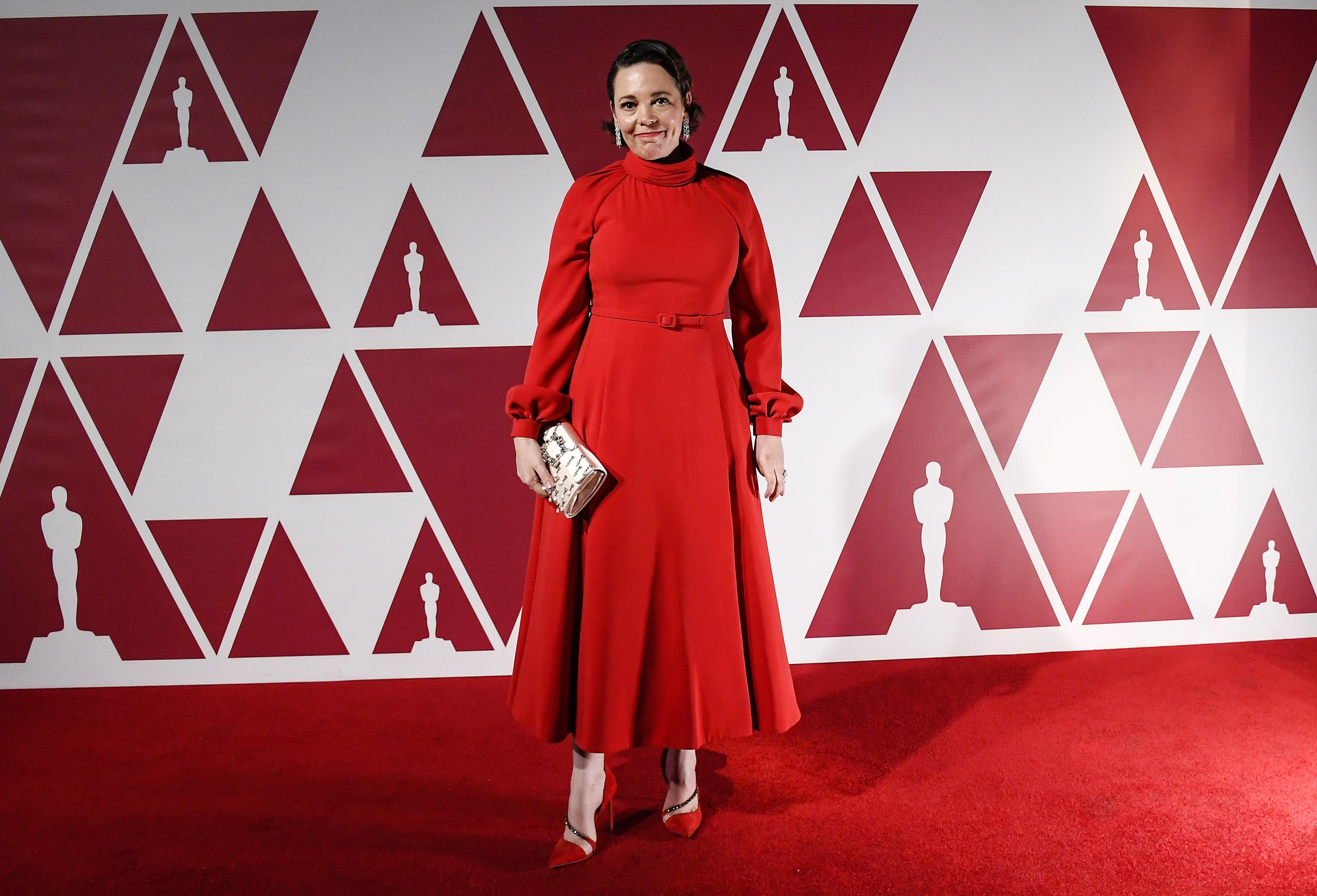 Olivia é uma mulher branca com cabelos castanhos curtos. Ela usa um vestido vermelho de mangas compridas e cinto da mesma cor. Carrega uma clutch branca.