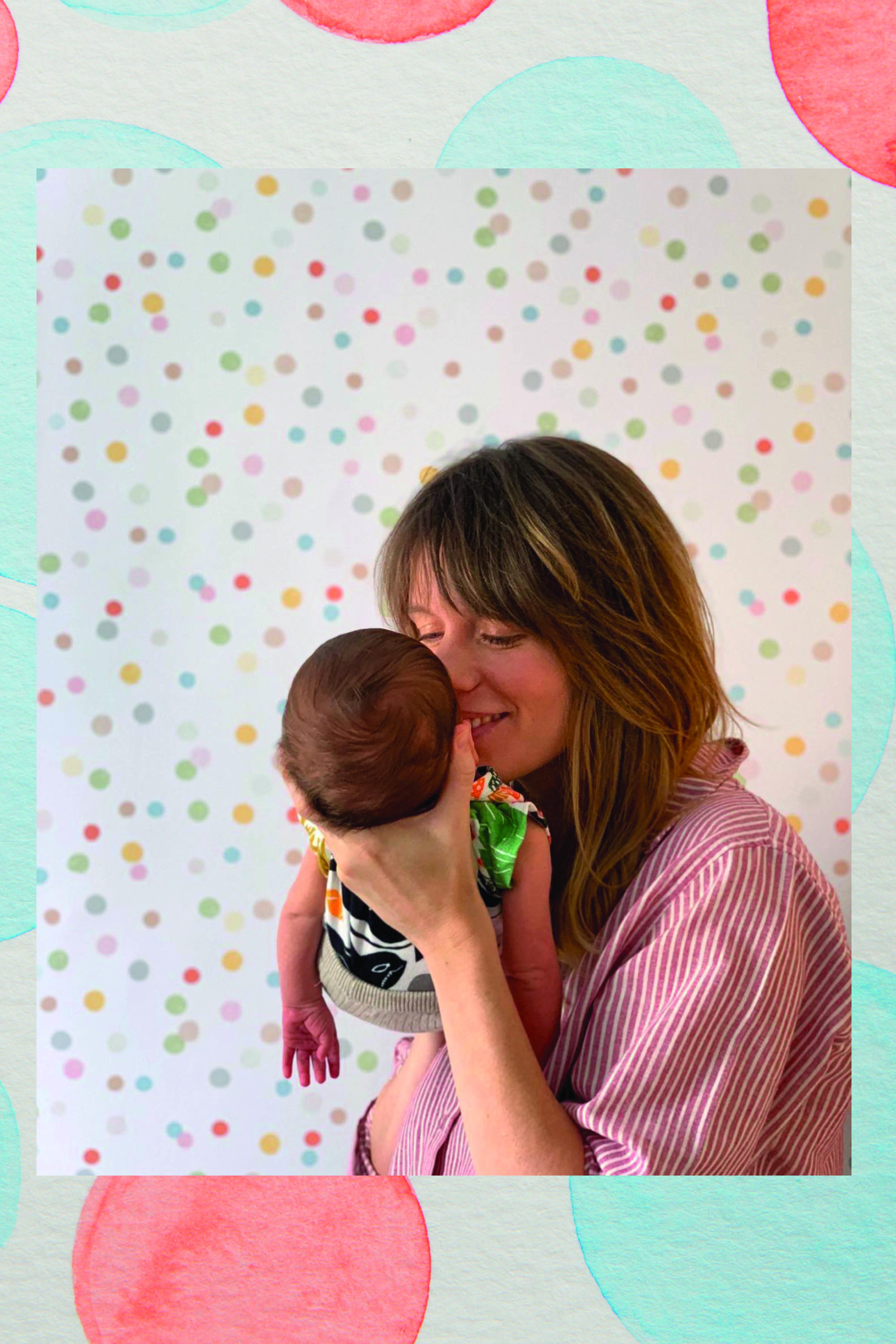 Laura segura o bebê no colo e beija seu rosto