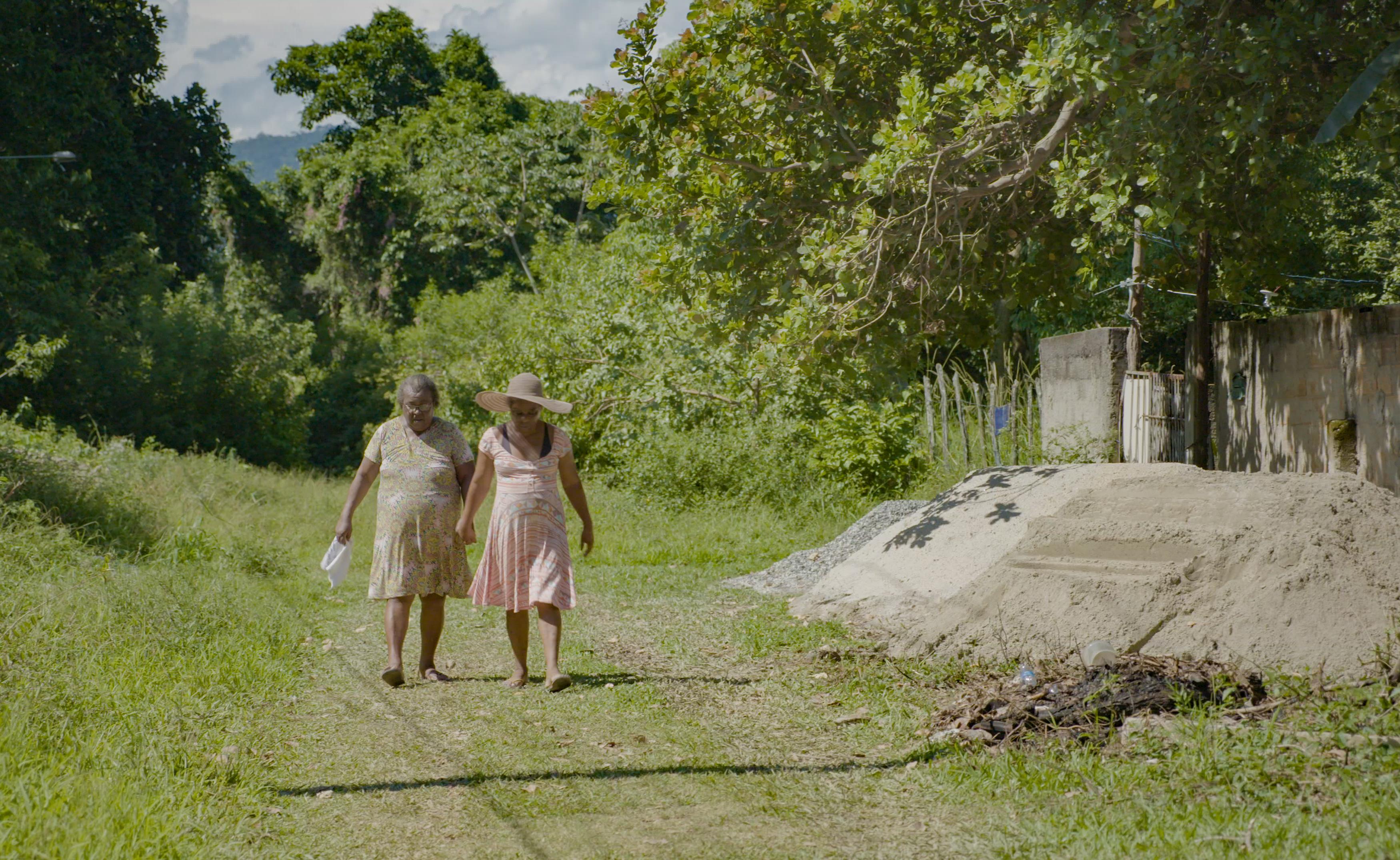 mulheres caminham de mãos dadas numa área rural