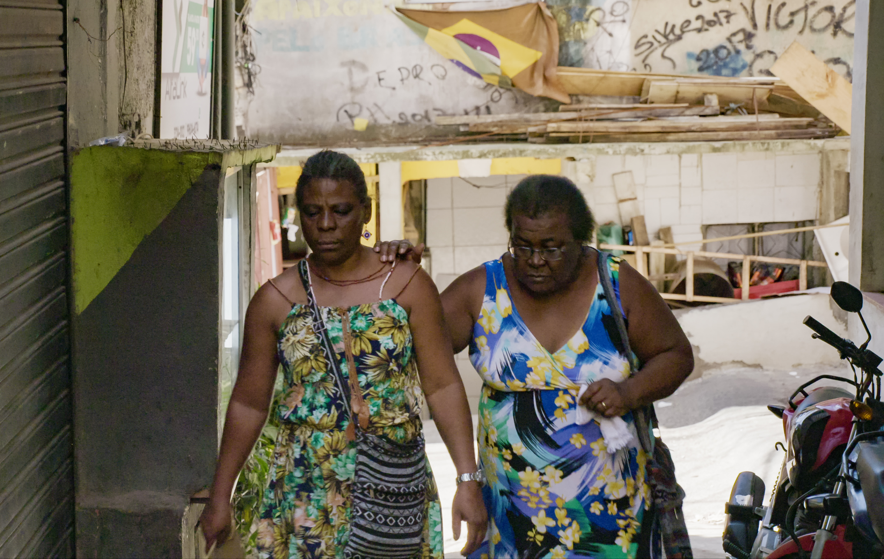 Casal de mulheres caminha pela rua com uma se apoiando na outra