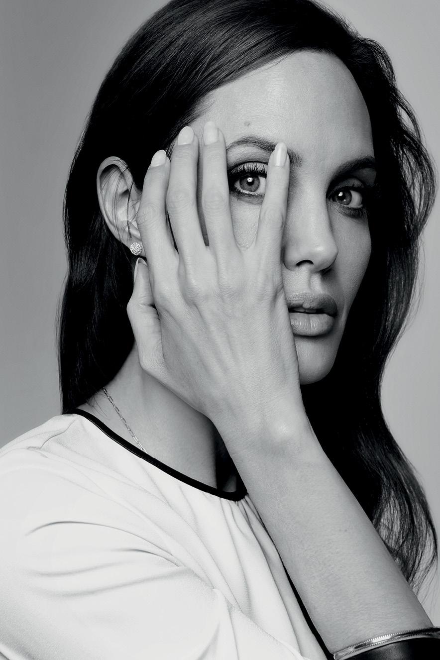Angelina Jolie com a mão no rosto permitindo ver seu olho por entre seus dedos