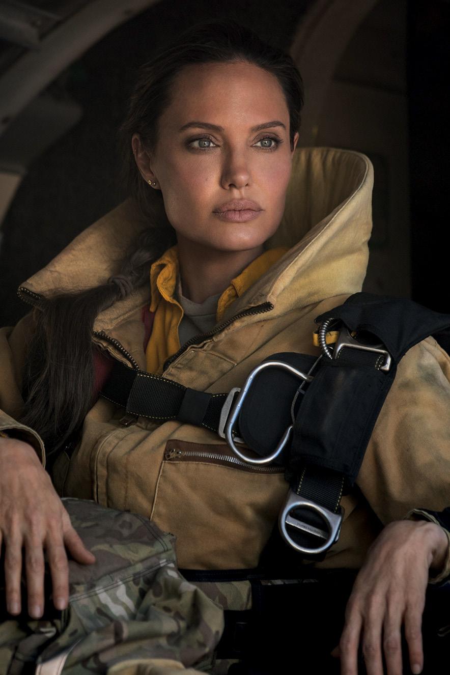 Angelina Jolie olha para o horizonte usando um grande casaco e usando cinto de segurança