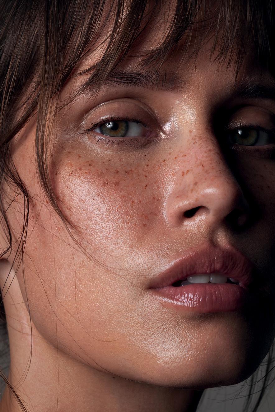 Em retrato, mulher maquiada com pele natural olha para a câmera