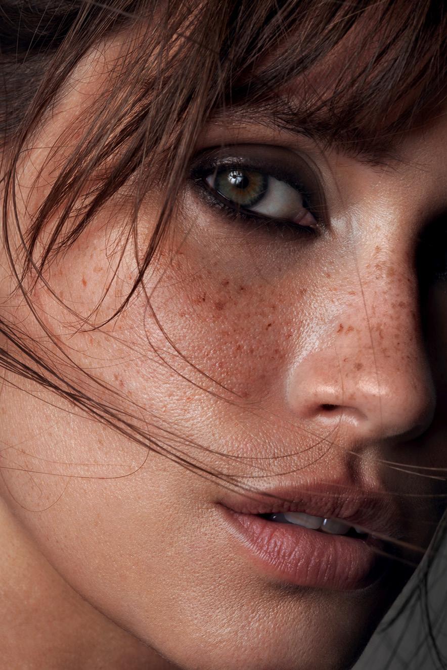 Em retrato, mulher maquiada com pele natural e olhos marcados por lápis preto olha para a câmera