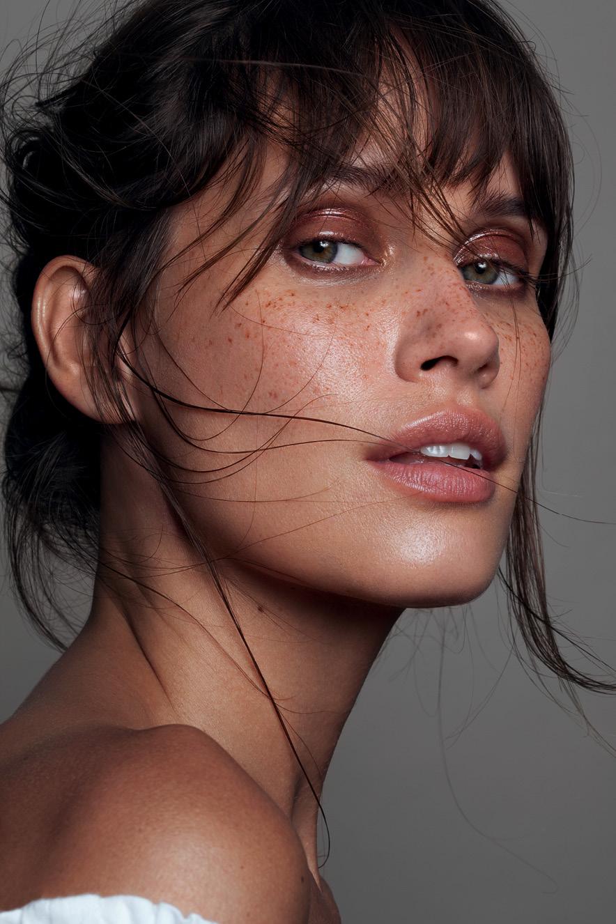Em retrato, mulher maquiada com pele natural e olhos marcados por sombra marrom olha para a câmera