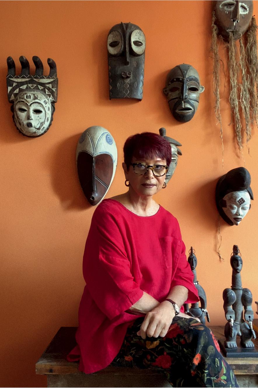 Na sala de sua casa, Julita olha para a câmera. Atrás dela há uma parede com máscaras africanas