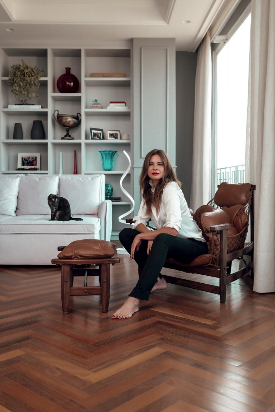 Luciana sentada numa poltrona em seu apartamento