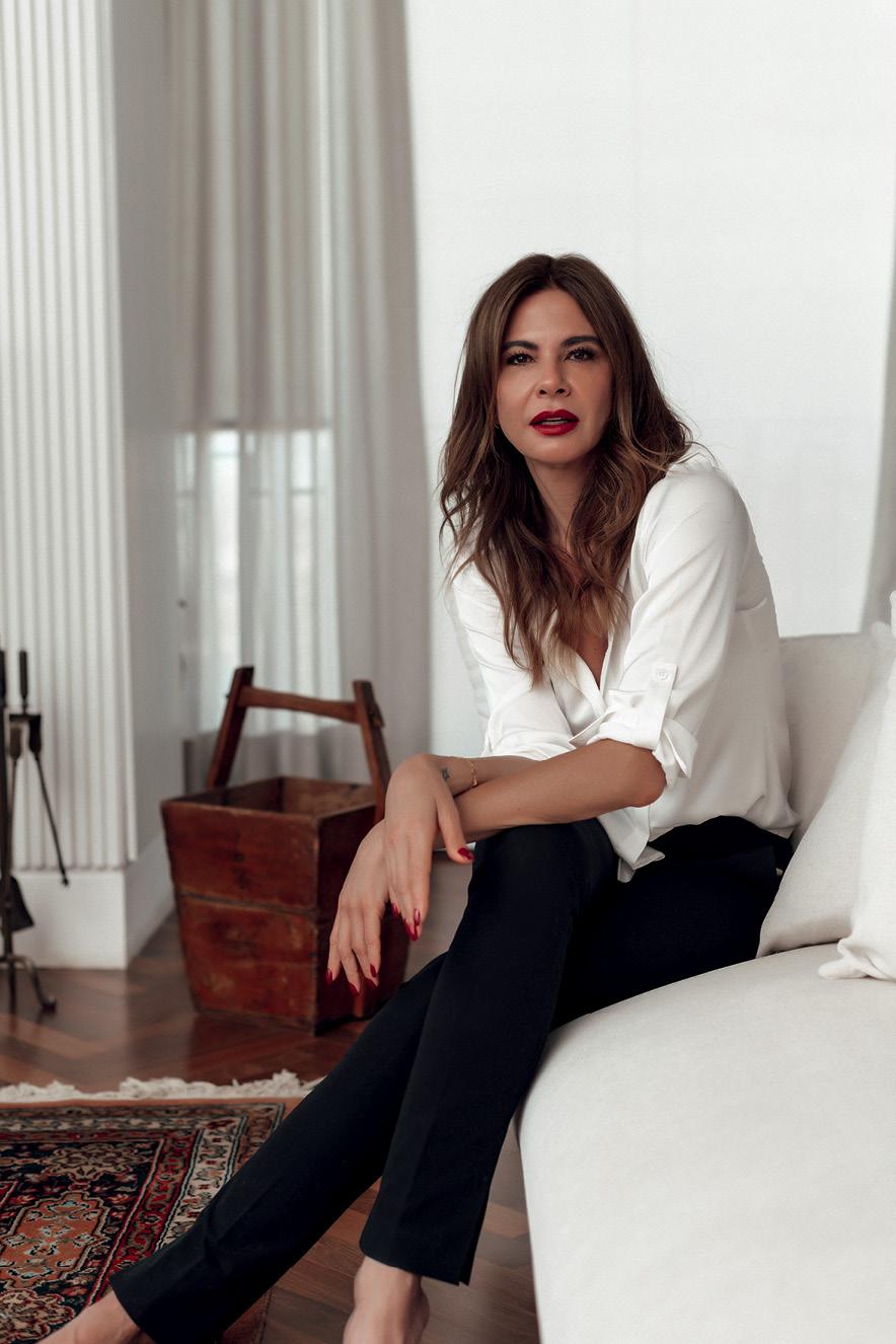 Luciana sentada no sofá em seu apartamento