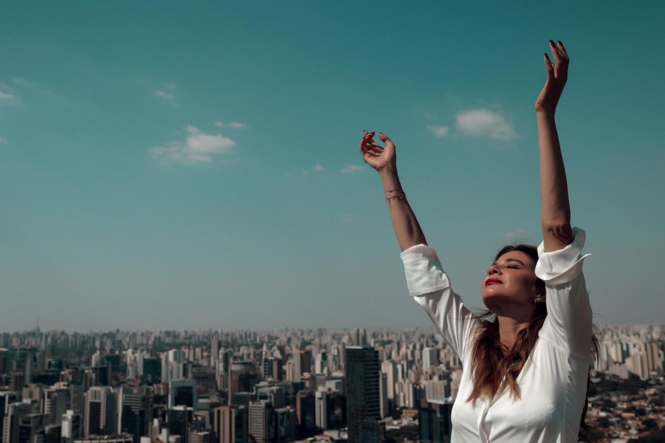 Luciana com os braços levantados em direção ao céu