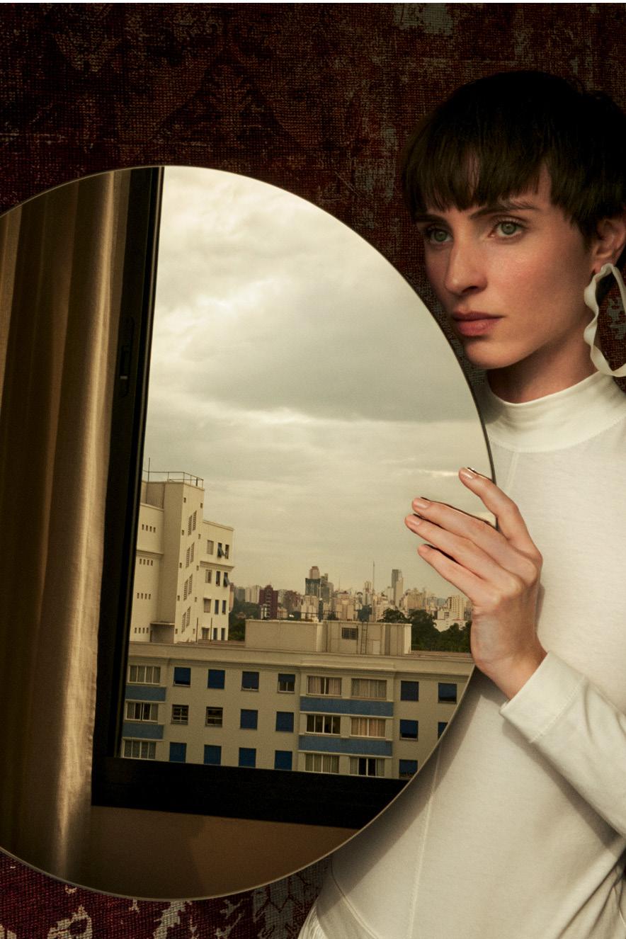 modelo com blusa branca segura um espelho