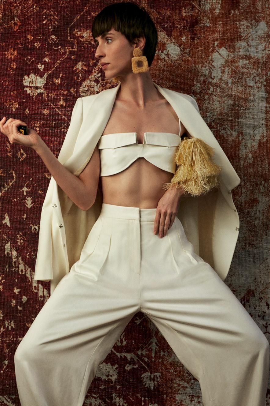 modelo com roupa branca e bolsa de palha