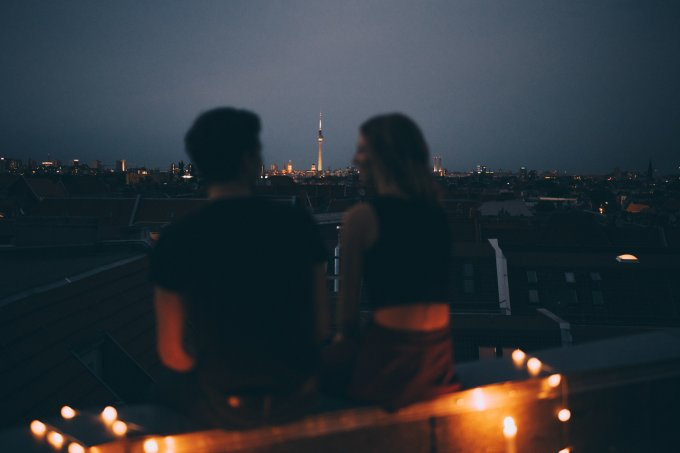 Rear view of couple sitting on terrace against cityscape at dusk