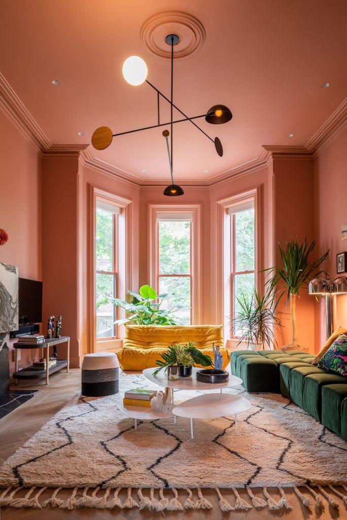 Sala com sofá amarelo e paredes pintadas com cor rosa