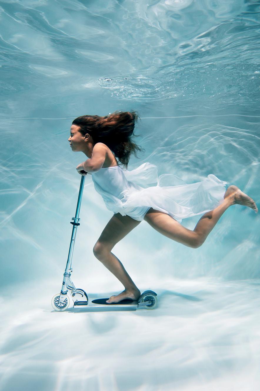 mulher andando de patinete debaixo da água