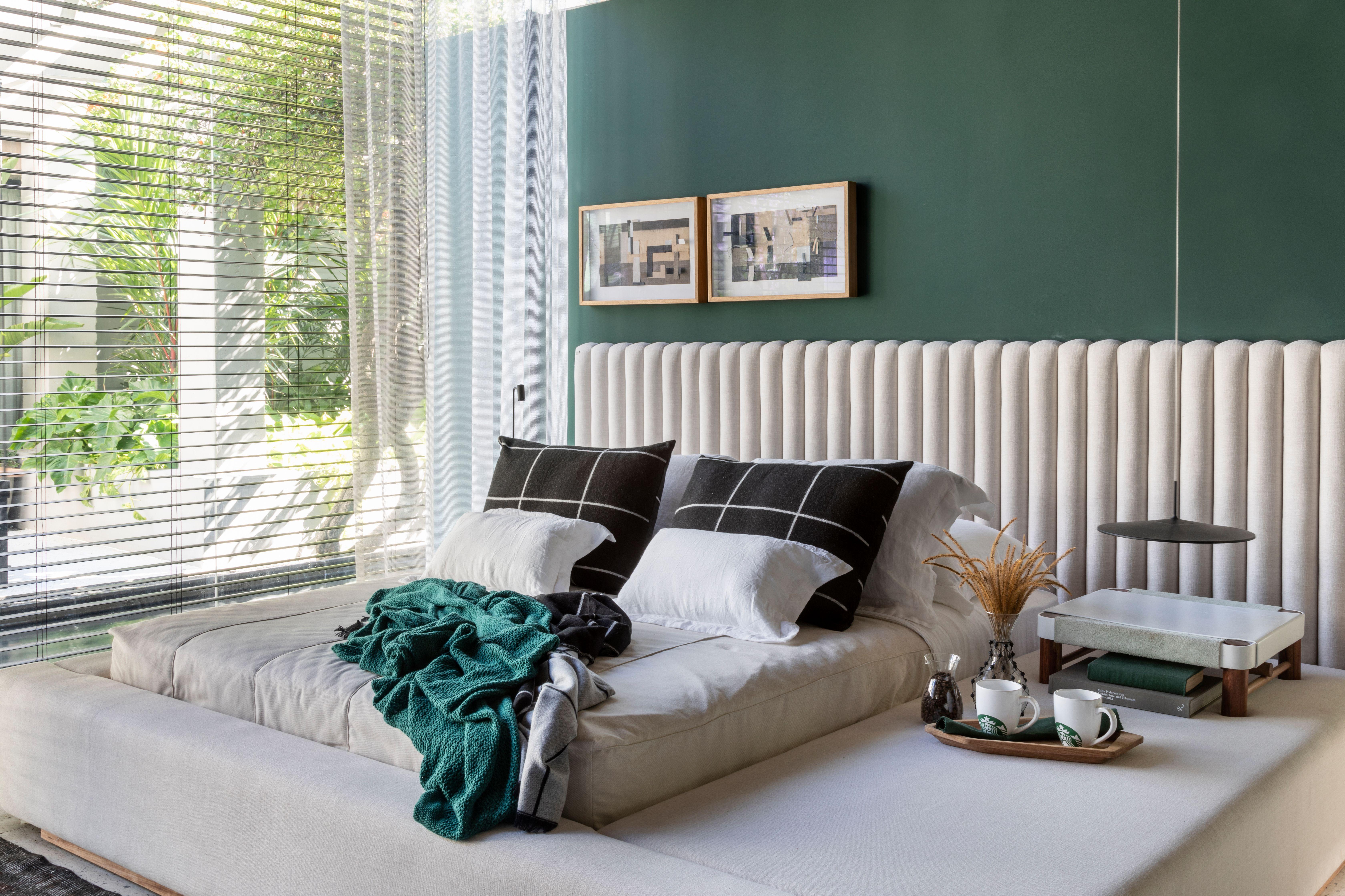 Quarto com parede verde e cama baixa