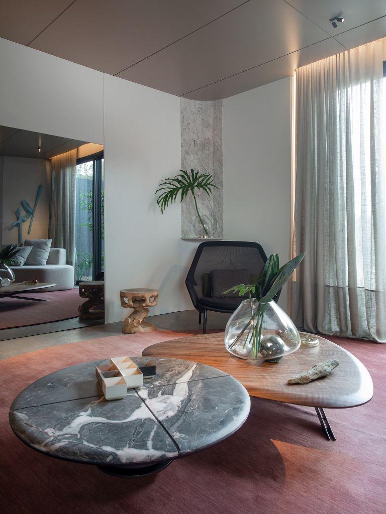 Sala de estar com tapete laranja e mesas de centro de pedra e madeira