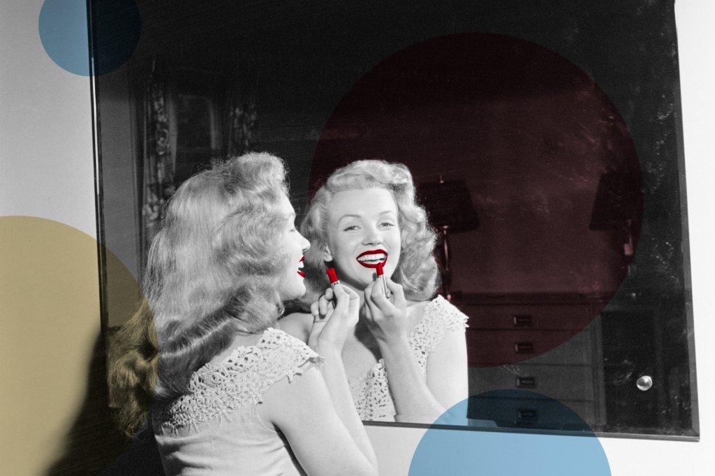 Marilyn Monroe de frente para o espelho passando batom vermelho e sorrindo.
