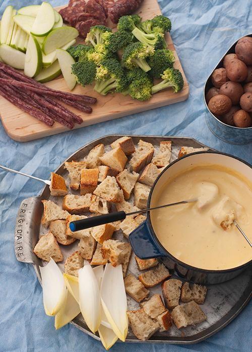 fondue de queijo servido em tábuas de metal e fôrmas