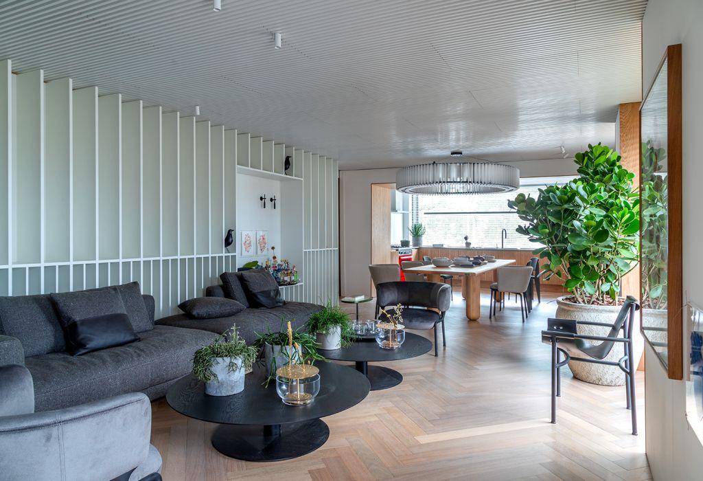 Um lounge integrado com plantas, luz natural e tons claros
