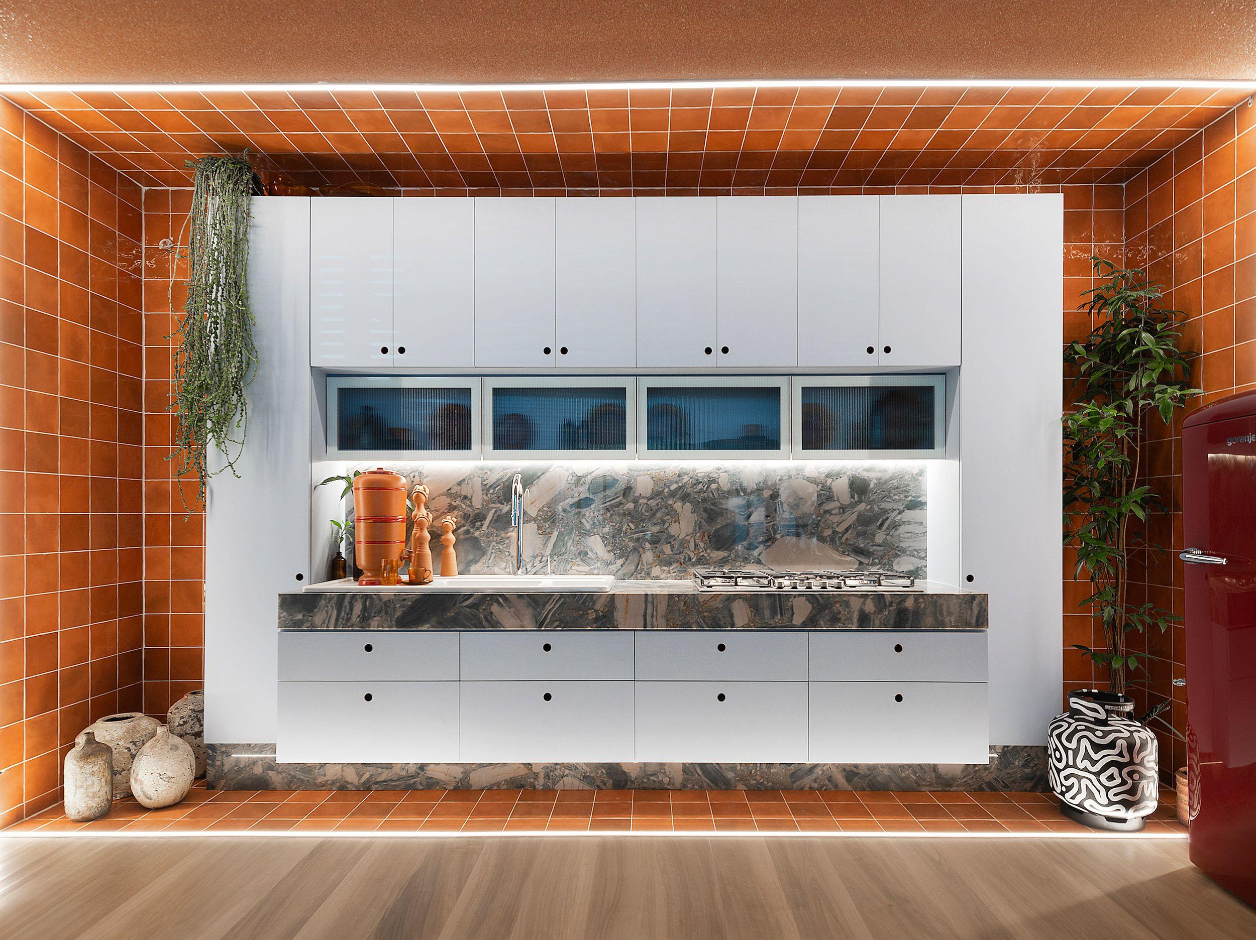 Cozinha com armários brancos e revestimentos em terracota