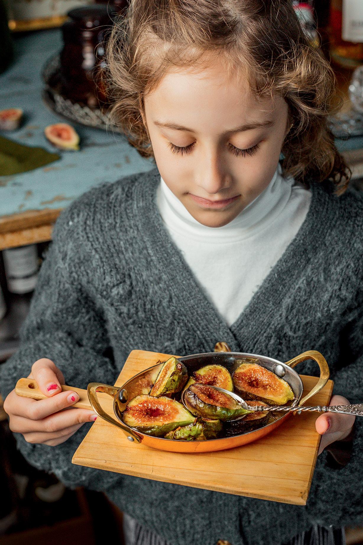 Menina olhando para prato de figos flambados
