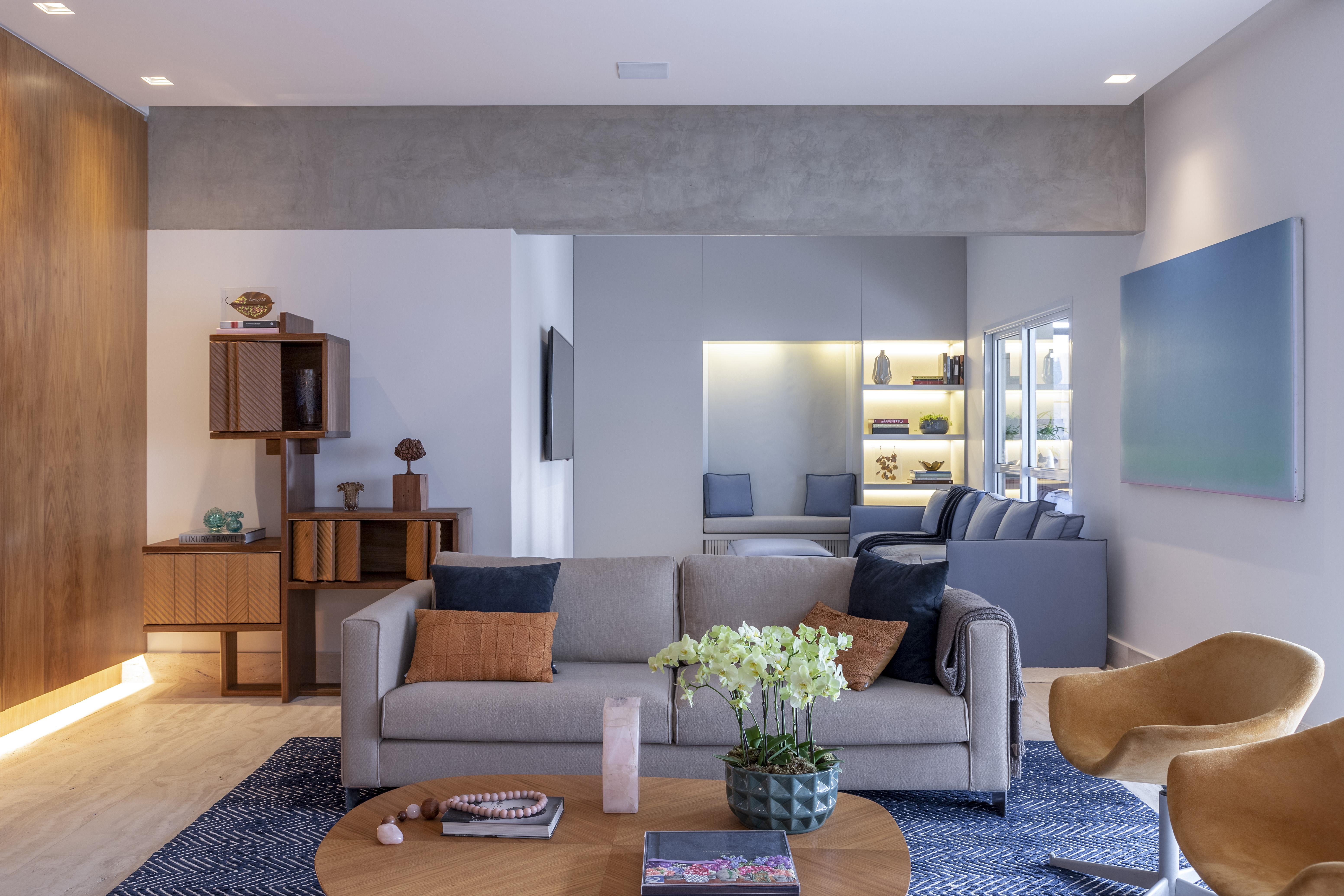 Sala de estar integrada com sofá cinza, tapete azul e mesa de madeira