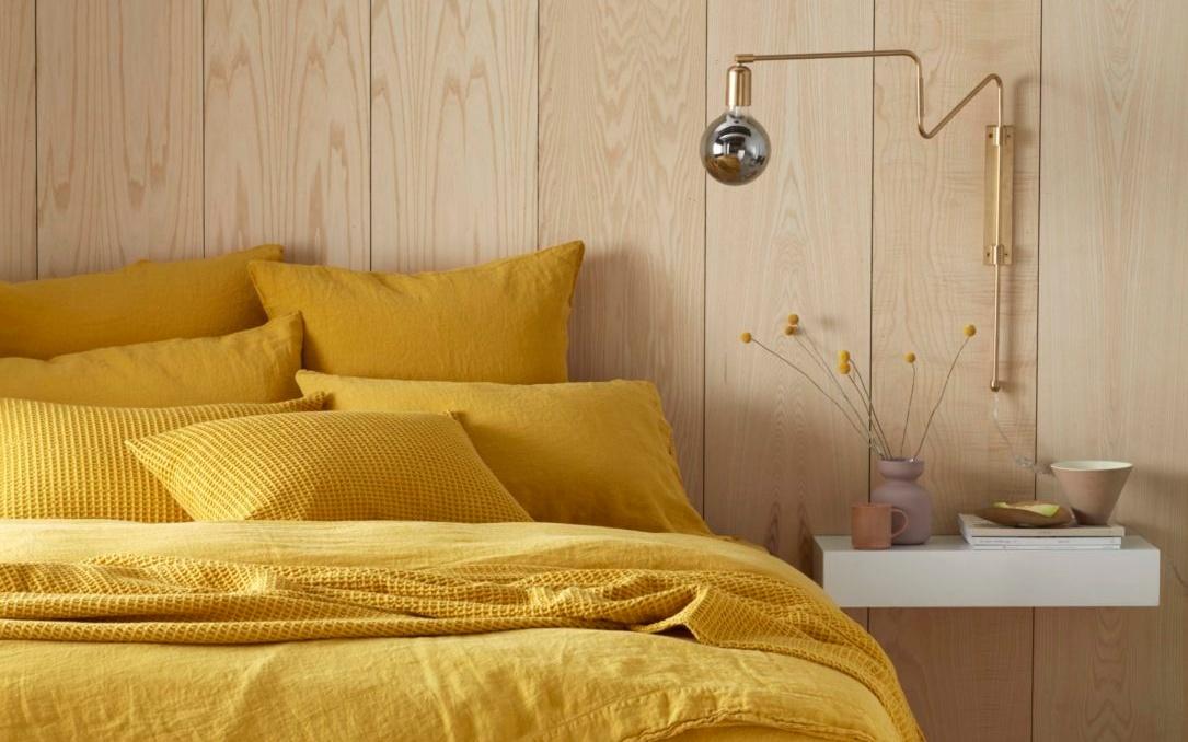 Cama com roupa de cama de linho amarela