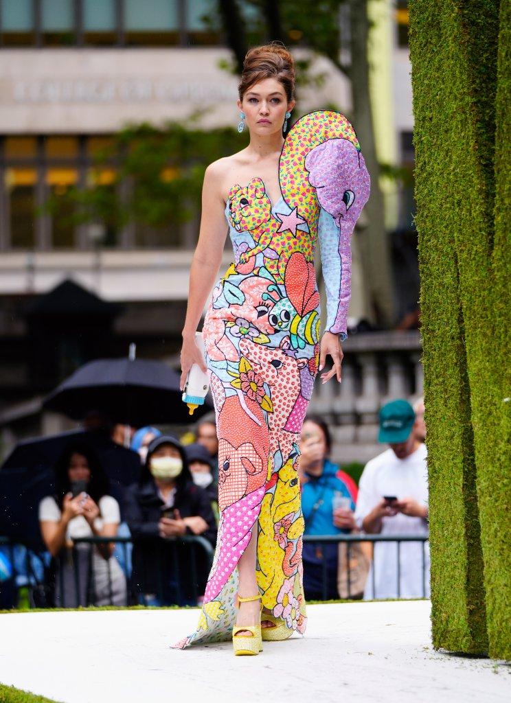 Modelo anda na passarela com um vestido colorido de um ombro só.