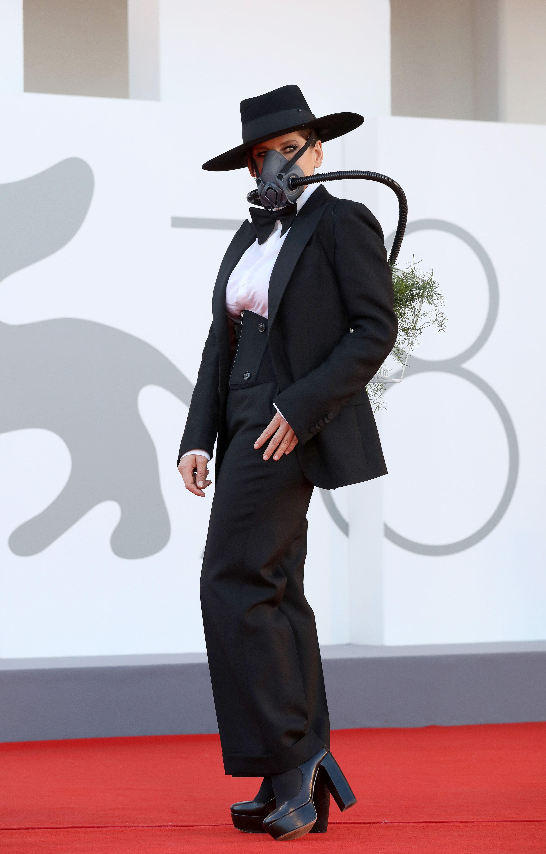 Barbara de paletó preto e máscara de proteção.