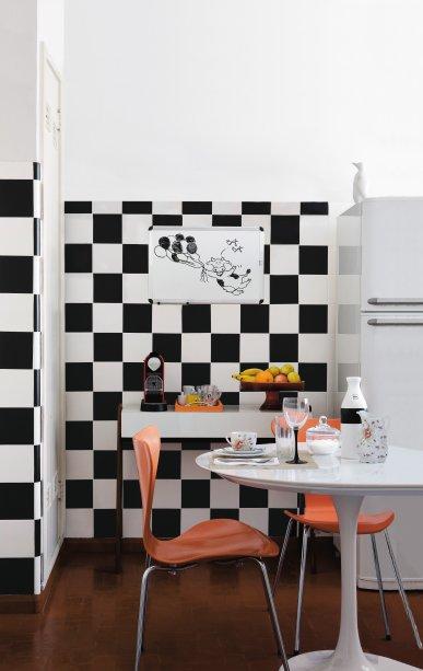 Parede montada com adesivos foscos pretos sobre azulejos na cozinha.